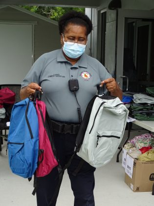 <p><p>A DeLand community service aide assists in backpack distribution.</p></p><p>BEACON PHOTO/MARSHA MCLAUGHLIN</p>