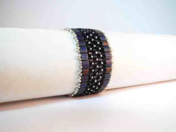 Two colours of seed beads woven in the diamond shape characteristic of netting stitch are enveloped by two rows of Tila beads in the Netted Cuff.