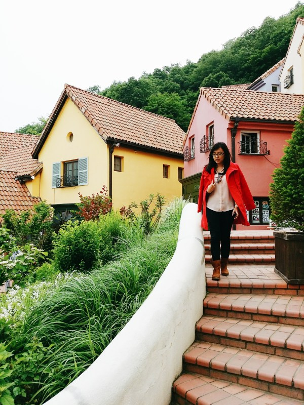 A girl in red coat going down the stairs with a yellow and pink house in the background