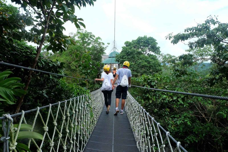 a couple on their back with masungi georeserve backpacks in a suspended bridge