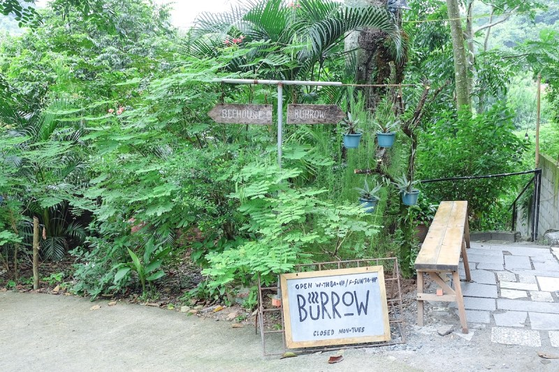 a green entrance with a small signage of Burrow Cafe Antipolo on the floor