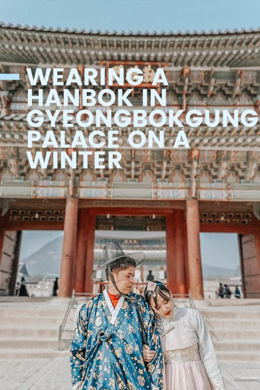 Couple wearing Korean traditional dress hanbok in front of a palace with text Wearing a hanbok in Gyeongbokgung Palace on a winter