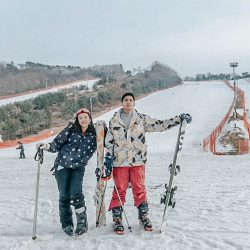 A couple with their ski equipment in the foot of a Vivaldi Ski World slope