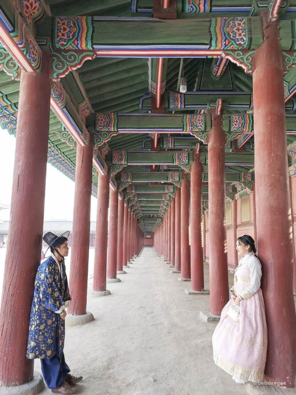 A Couple wearing a traditional Korean Hanbok looking at each other in a Korean palace setting