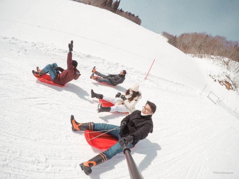 4 people in a snow sleds in gala yuzawa