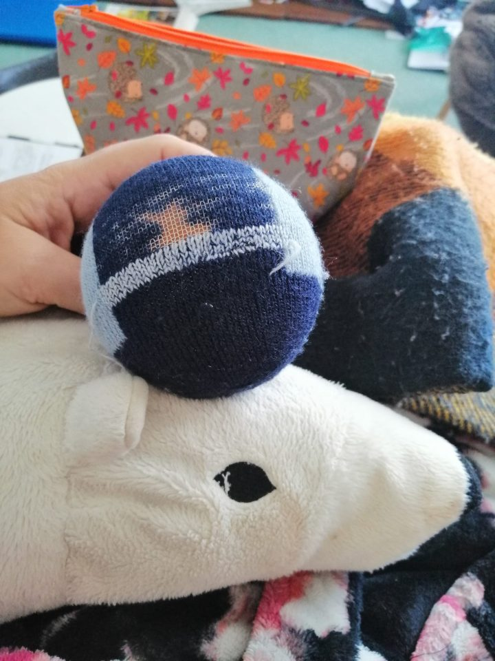 a few rows of pale blue darning on a dark blue thermal sock, resting on the head of a polar bear teddy from IKEA