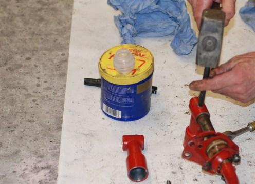 Het verwijderen van de spanas door middel van een doorslag en hamer.