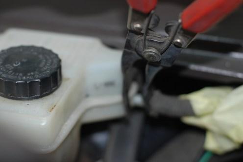 De klipstang als hulp bij het verwijderen van de koppelingsslang.