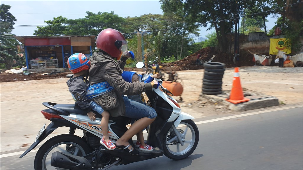 An adult and two small children on a scooter