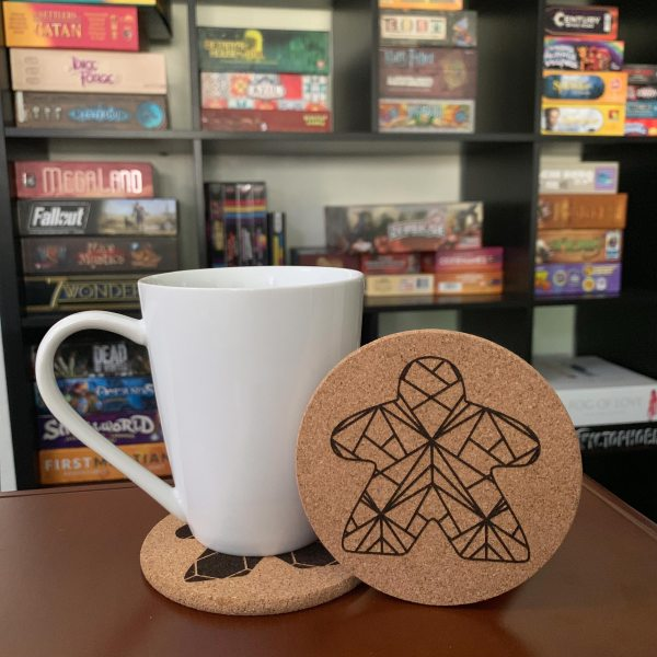 Closeup of Mug and Meeple Facets Coaster in front of Kallax Board Game Shelf