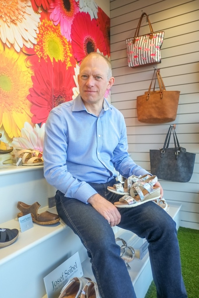 image of Briggs shoes owner Tom Powney in the Briggs Shoes shop window