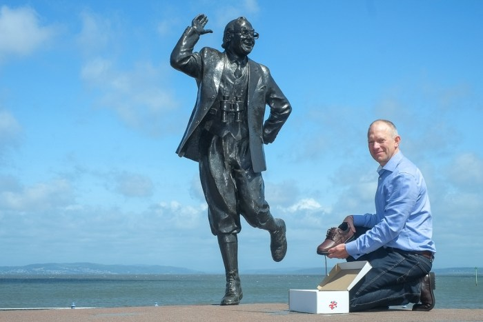 image of Briggs shoes owner Tom Powney beside the Eric Morecambe statue