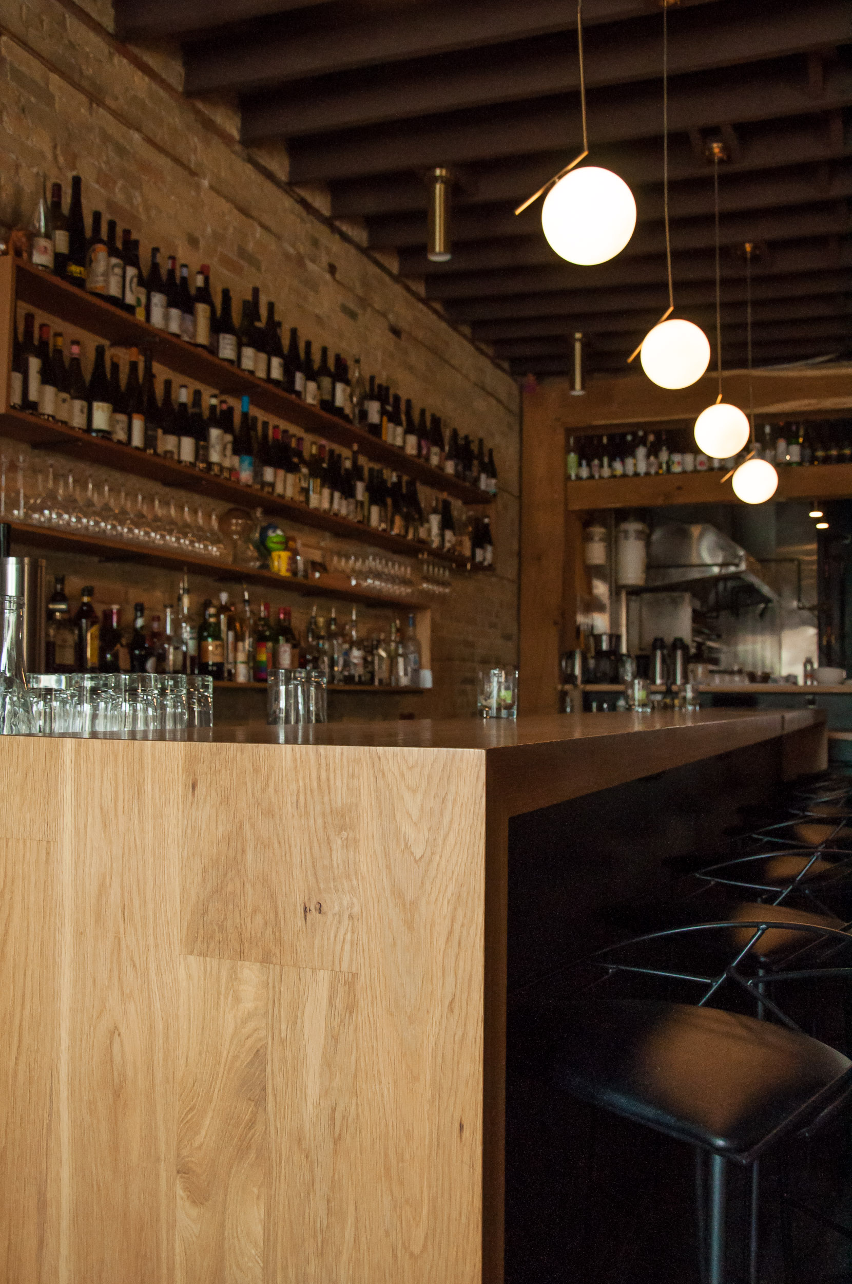 Close-up of custom bar top and back shelving made with White Oak for The Oxbow Natural Wine Bar & Restaurant