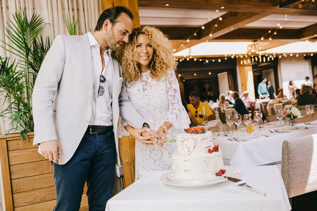 A bride and groom cutting their wedding cake.