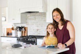 Mom and Daughter in new kitchen renovation with white backsplash and white kitchen cabinets