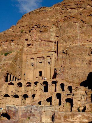 Petra's Royal Tombs with bedouins sitting above - by Anika Mikkelson - Miss Maps - www.MissMaps.com