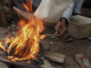 Staying Warm, Foot in Fire - Varanasi, India - by Anika Mikkelson - Miss Maps