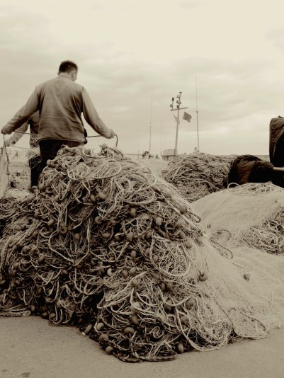 A fisherman readies his nets in Kundalasi, Turkey - by Anika Mikkelson - Miss Maps