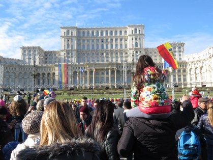 Proudly waving Romania's flag outside the Palace of Parliament - - Bucharest Romania - by Anika Mikkelson - Miss Maps - www.MissMaps.com