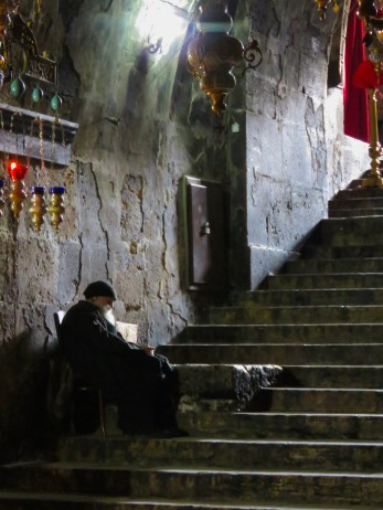 A priest waits on the steps of Church of the Sepulchre of Saint Mary in Jerusalem Israel - by Anika Mikkelson - Miss Maps - www.MissMaps.com
