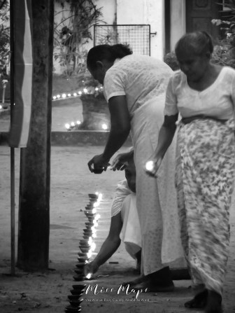 Women Lighting Candles at the Buddhist Temple on New Years Day - Galle Sri Lanka - by Anika Mikkelson - Miss Maps - www.MissMaps.com