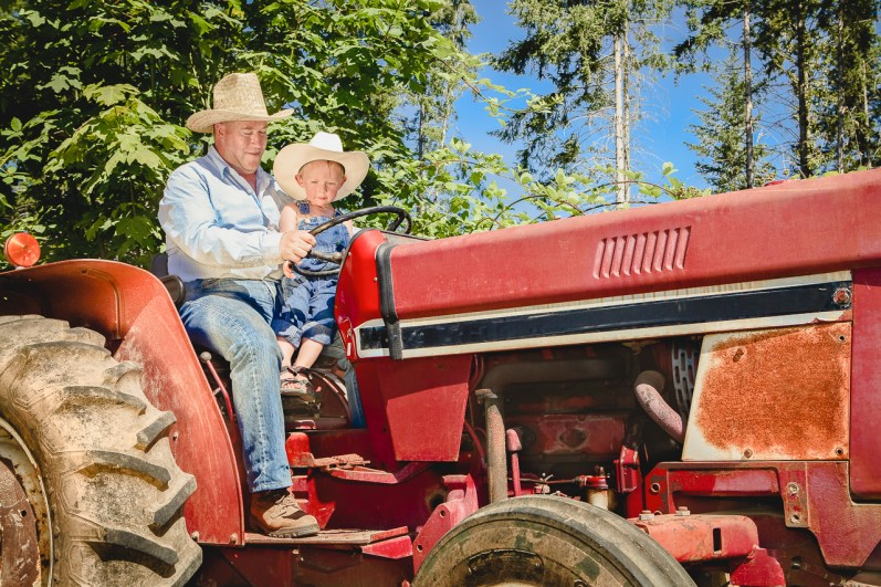 Old farmer giving little boy ride on a red tractor
