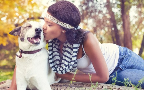 Smiling dog getting a kiss from a beautiful girl