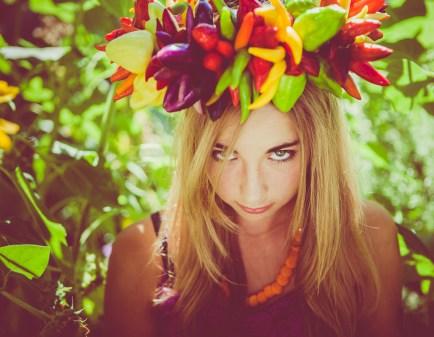 Pretty girl wearing crown of hot peppers in summer garden