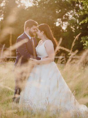 Bride & groom in a long grass field during golden sunset