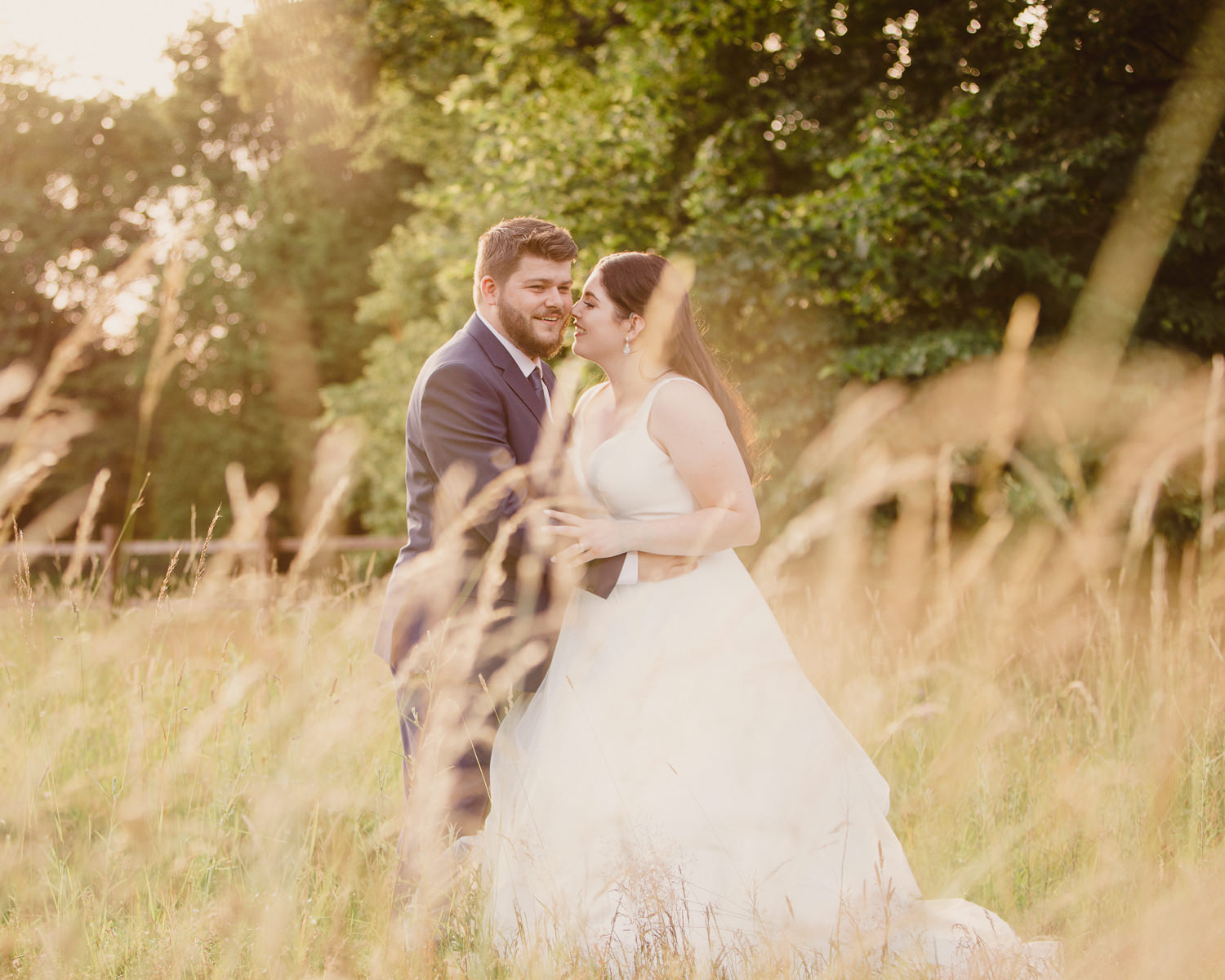 Bride & groom in a field with long grass in golden evening light