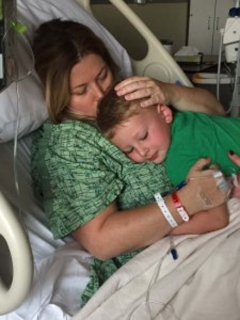 Son hugging his mom in a hospital bed