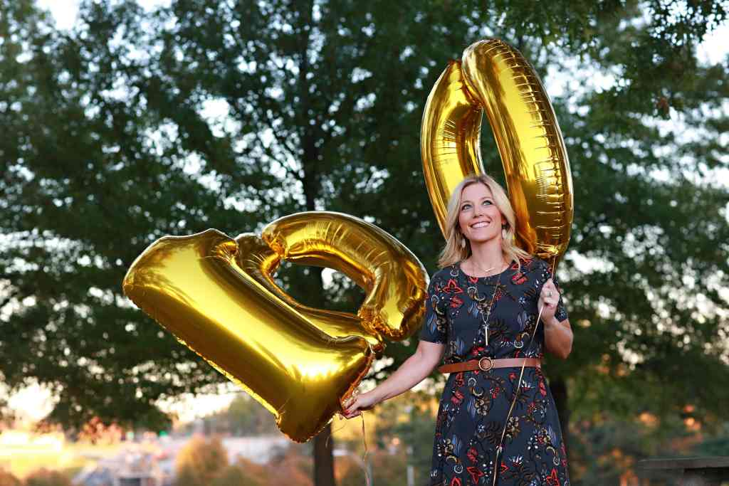 Amy holding 100 balloons