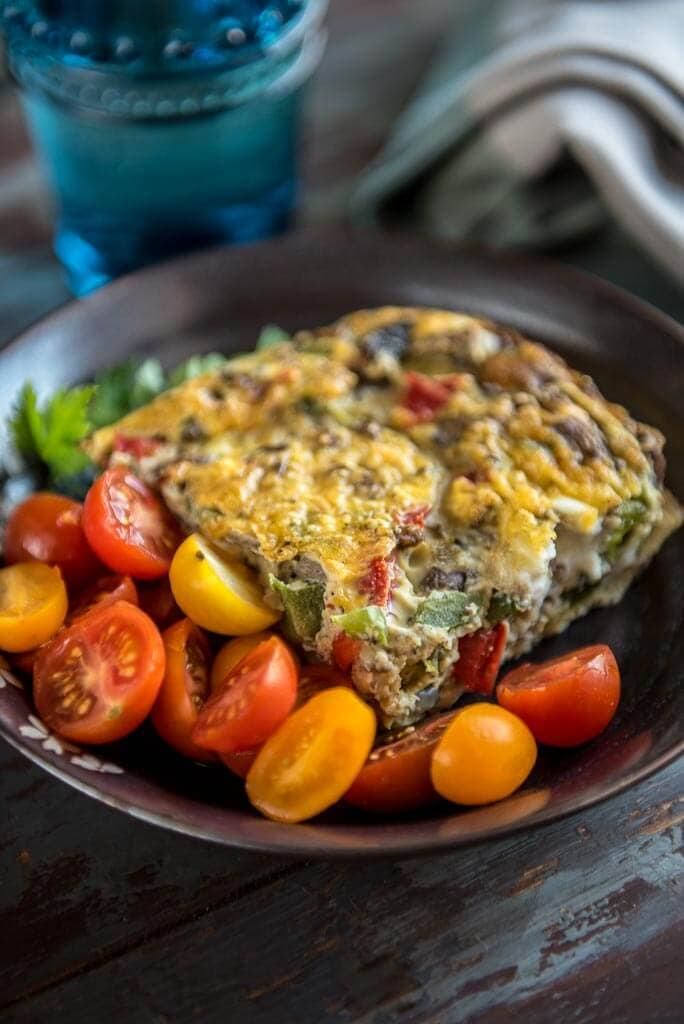 Healthy Breakfast Casserole with vegetables on a black plate with tomatoes