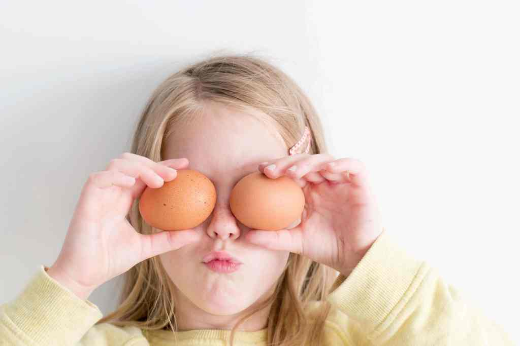 Little girl putting eggs over her eyes