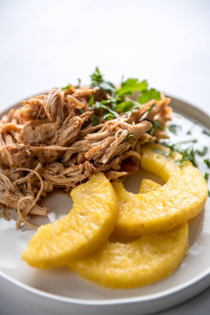 Slow Cooker Salsa Chicken on a white plate garnished with pineapple slices and cilantro