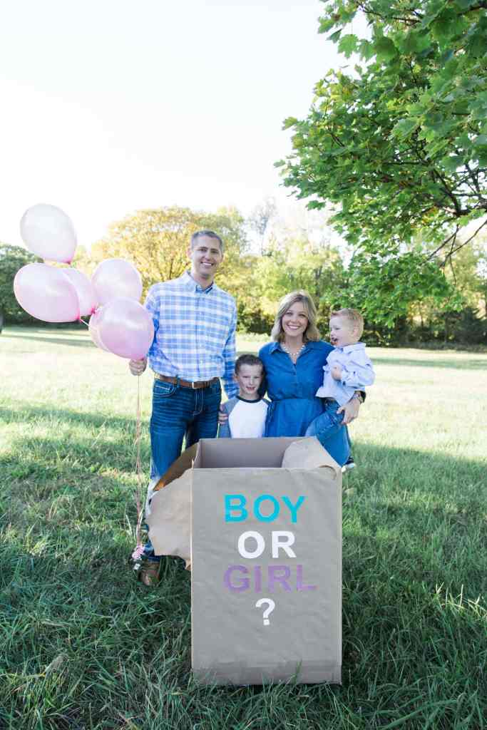 A family of four with a box holding pink balloons for their gender reveal