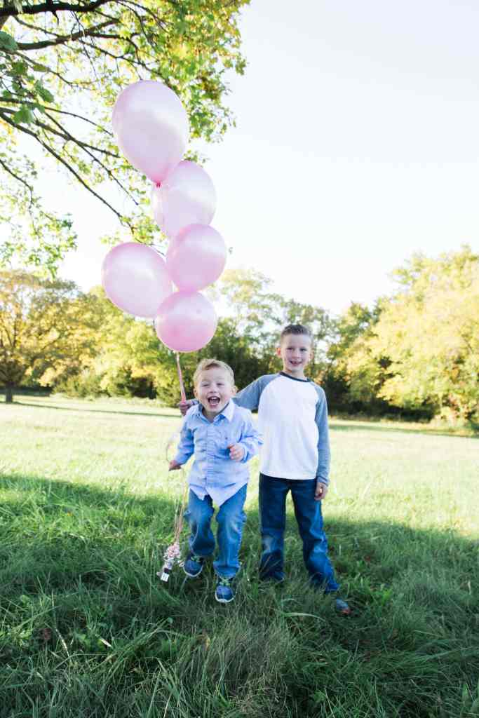 Two boys holding pink balloons for gender reveal