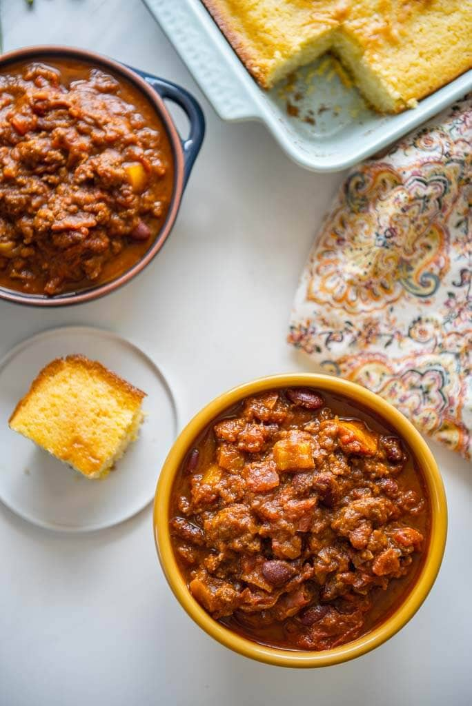 Overhead shot of 2 bowls of Pumpkin Chili and a piece of cornbread that is cut and a pan of cornbread.
