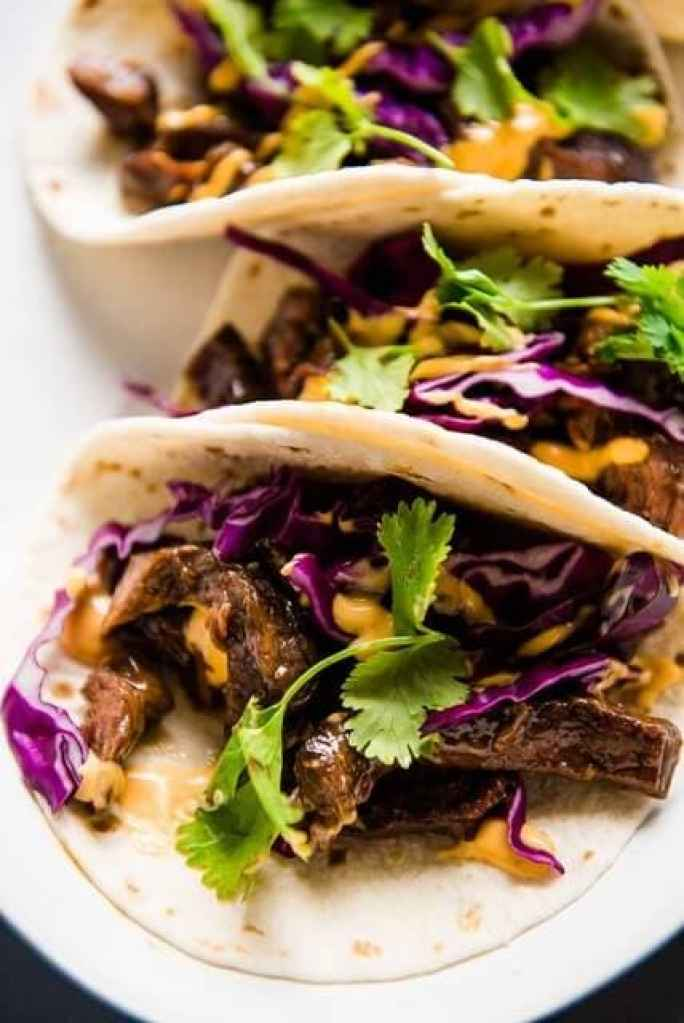 Close up picture of korean beef tacos with cabbage and cilantro