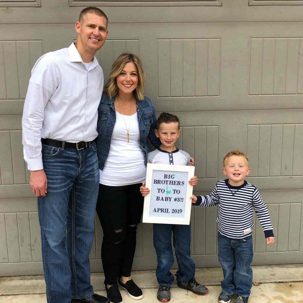 A family of four announcing they are having a baby.