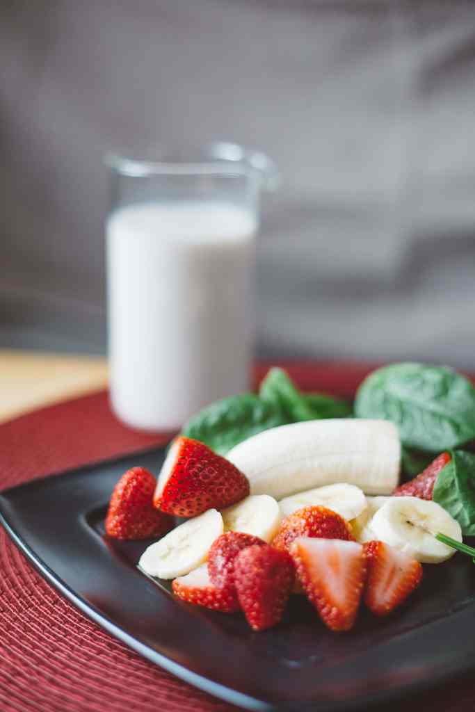 A plate with fruit on it and a glass of milk