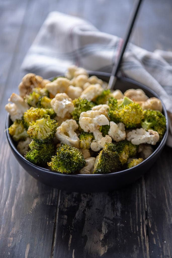 Roasted broccoli and cauliflower on a wooden table in a black bowl with a spoon and white napkin