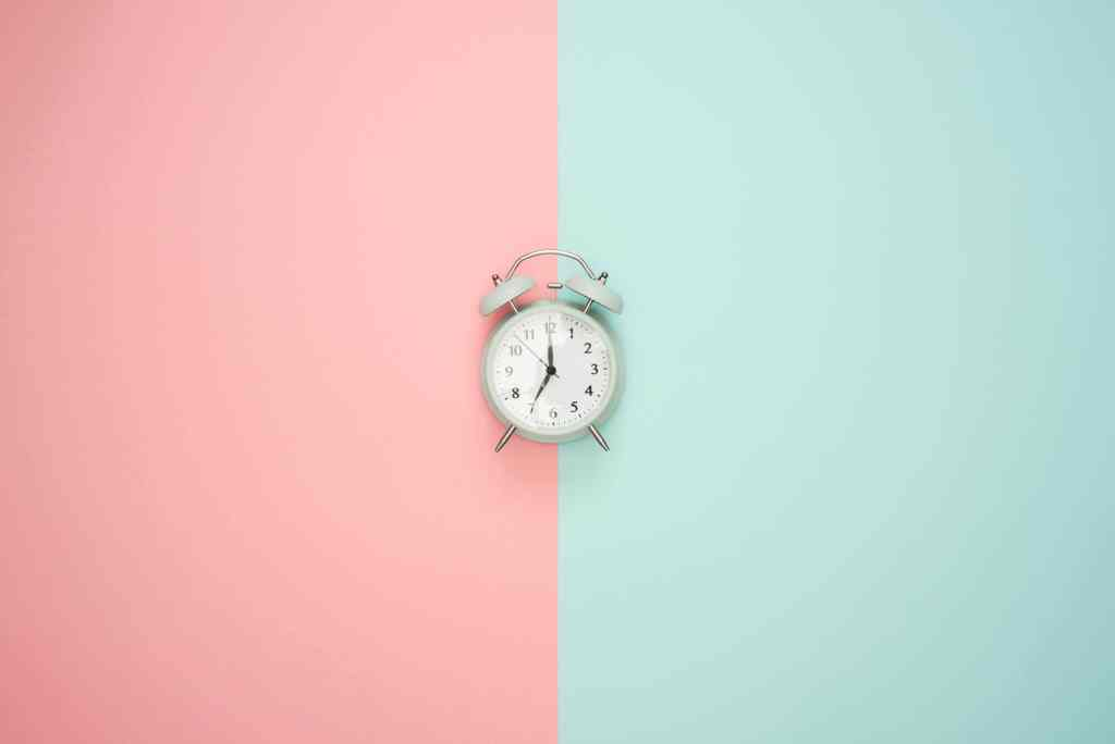 A clock with a pink and blue background