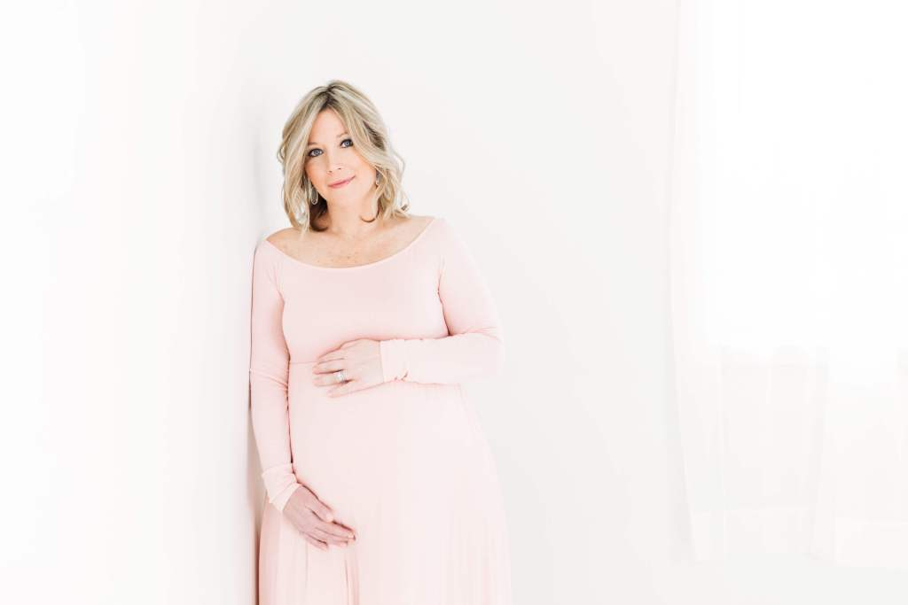 Pregnant woman in a light pink dress holding her tummy