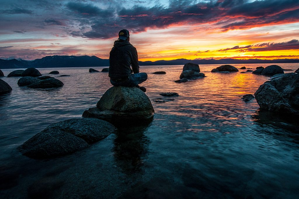 person sitting on rock on body of water 1478685 scaled