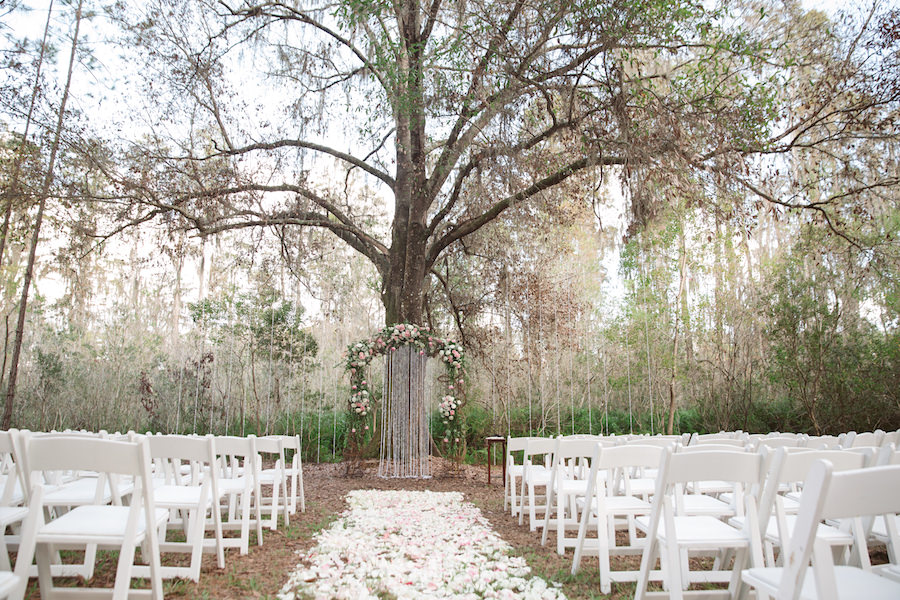 Rustic Outdoor Wedding Ceremony with Light Pink and White Floral Archway under Tall Pines with White Resin Folding Chairs and Rose Petal Aisle | Tampa Bay Wedding Floral Designer Northside Florist
