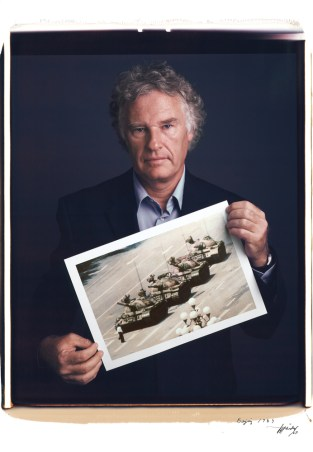 Jeff Widener holds his photo of Tank Man in Tienanmen Square from 1989.