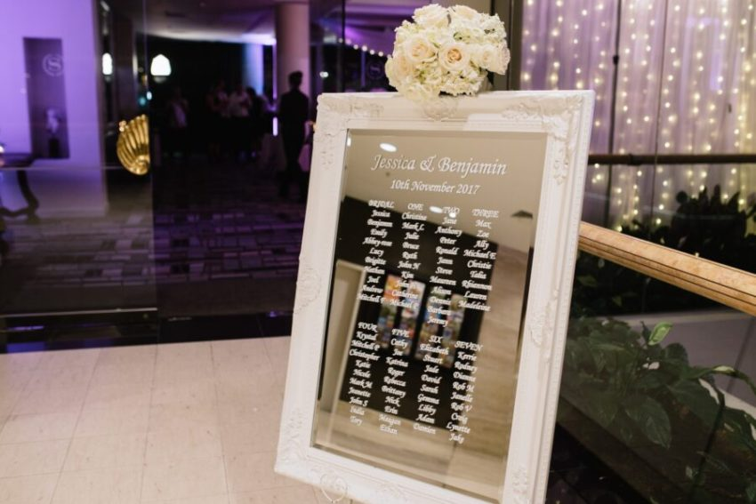 Jess-&-Ben-sheraton-grand-mirage-wedding-reception-seating-plan-chart-white-baroque-mirror-frame-welcome-sign