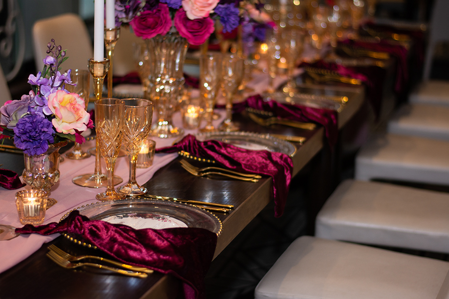 blackbird-wedding-reception-styling-amber-crystal-stemware-candlestick-holders-bright-faux-silk-flower-floral-arrangement-burbundy-velvet-napkins-gold-beaded-glass-charger-plates-blush-chiffon-table-runner