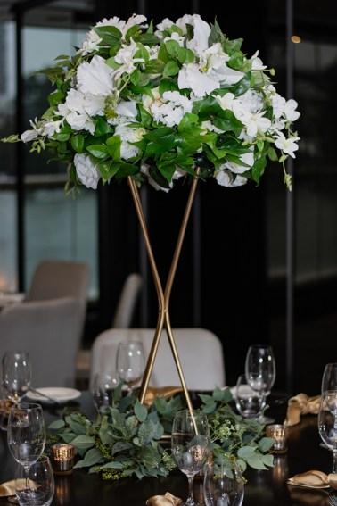 blackbird-wedding-reception-styling-gold-stand-faux-silk-greenery-&-white-floral-topper-table-centrepiece